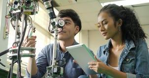 Edificio joven asiático del ingeniero electrónico, robótica de la fijación en laboratorio almacen de video