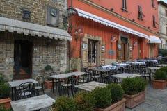 Edificio medieval con el balcón y puertas anchas en el cuadrado de ciudad central rodeado con el café de la calle en el alto de fotografía de archivo libre de regalías