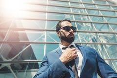 Edificio moderno de Wears Sunglasses Before del hombre de negocios barbudo foto de archivo