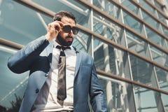 Edificio moderno de Wears Sunglasses Before del hombre de negocios barbudo imagenes de archivo