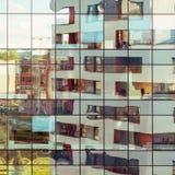 Edificio moderno reflejado en la fachada de cristal Imágenes de archivo libres de regalías