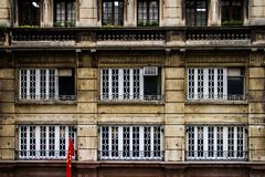 Edificio per uffici invecchiato con la bandiera del cinese nella parte anteriore immagini stock libere da diritti