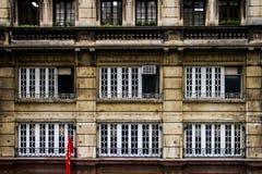 Edificio per uffici invecchiato con la bandiera del cinese nella parte anteriore Fotografia Stock Libera da Diritti
