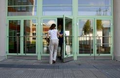 Edificio que entra de la muchacha imágenes de archivo libres de regalías