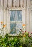 Edificio rústico con una ventana vieja resistida y flores anaranjadas en frente, en el parque de estado taconic Imagenes de archivo