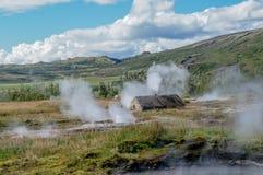 Edificio rústico rodeado por las aguas termales en el valle de Haukadalur cerca de Geysir, Islandia Imágenes de archivo libres de regalías