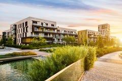 Edificio residencial en el parque verde público durante salida del sol Fotos de archivo libres de regalías