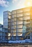 Edificio residenziale demolito con i sacchetti di plastica e dell'escavatore riempiti di macerie nella priorità alta, soleggiata  Fotografia Stock