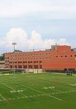 Edificio scolastico con il campo di football americano immagini stock libere da diritti
