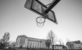 Edificio scolastico di vecchia scuola e potography in bianco e nero del cerchio di pallacanestro Immagini Stock Libere da Diritti