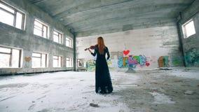Edificio trenzado con la pintada y una mujer que toca el violín metrajes