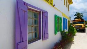 Edificio tropical del estilo de Bahama con el autobús escolar Fotos de archivo libres de regalías