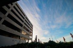 Edificio vacante vacío del aparcamiento con el cielo azul y el jardín local imagen de archivo