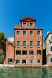 Edificio veneciano rojo por el agua en Venecia, Italia fotos de archivo