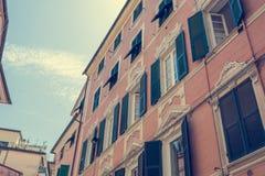 Edificio viejo con la fachada roja y las ventanas verdes Imagen de archivo libre de regalías