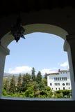 Edificio y jardín blancos en marco de ventana Imágenes de archivo libres de regalías