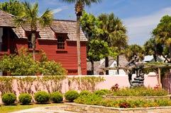 Edificio y jardín rojos viejos Foto de archivo libre de regalías