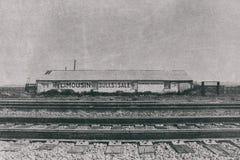 Edificio y plumas del rancho a través de pistas de ferrocarril Fotografía de archivo