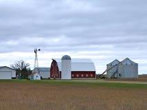 Edificios agrícolas con el molino de viento activo en un día nublado en Minnesota fotografía de archivo