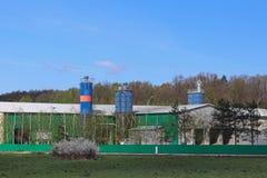 Edificios agrícolas entre los campos Fábrica situada en el paisaje natural Edificios técnicos cerca del bosque y de los campos co imagenes de archivo