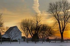Edificios agrícolas rurales con puesta del sol colorida Imagen de archivo