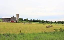 Edificios agrícolas y campo del heno fotos de archivo
