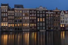 Edificios altos en Amsterdam, con las luces de las ventanas que reflejan en el agua tranquila del canal imágenes de archivo libres de regalías