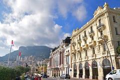 Edificios coloniales interesantes del estilo a lo largo de la carretera principal del principado de Mónaco con la bandera roja y  Imágenes de archivo libres de regalías