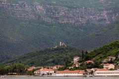 Edificios costeros con la iglesia de la cumbre en Montenegro Foto de archivo