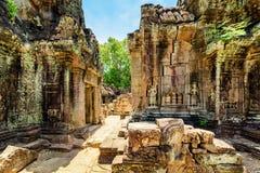 Edificios cubiertos de musgo antiguos con la talla del templo del som de TA en Angkor Foto de archivo