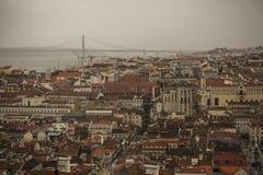 Edificios de Lisboa que miran abajo, 25 de Abril Bridge Foto de archivo