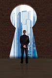 Edificios de Looking At City del hombre de negocios a través del agujero de la cerradura imagen de archivo libre de regalías