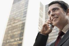 Edificios de oficinas de Using Cellphone Against del hombre de negocios imágenes de archivo libres de regalías