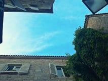 Edificios de piedra viejos asombrosos, ventanas de madera blancas y cielo azul imagenes de archivo