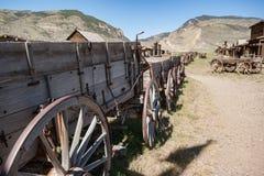 Edificios de registro del oeste viejos abandonados y carros de madera Imagen de archivo libre de regalías