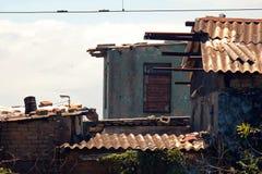 EDIFICIOS DESCOLORADOS DE DECAIMIENTO Y PLACAS DE TEJADO AHERRUMBRADAS EN PREMISAS INDUSTRIALES foto de archivo libre de regalías
