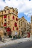 Edificios en La Valeta y la cabina de teléfono roja - La Valeta, Malta imagen de archivo