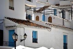 Edificios encantadores y puertas y ventanas azules en Frigiliana - pueblo blanco español Andalucía Foto de archivo