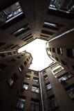 Edificios estrechos bien en St Petersburg con el cielo sobre los tejados Debajo de la visión Imagen de archivo libre de regalías
