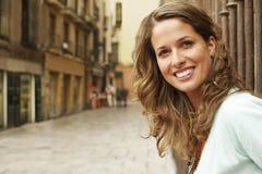 Edificios exteriores derechos sonrientes de la mujer en calle Fotos de archivo