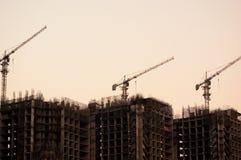 3 edificios inferiores de la construcción con las grúas tiraron en la oscuridad Foto de archivo