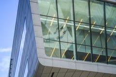 Edificios modernos de formas inusuales del vidrio y del metal Geometr?a de l?neas y de curvas La fachada inclinada Cielo azul fotos de archivo libres de regalías