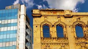 Edificios modernos y viejos con gran lapso de tiempo de las nubes