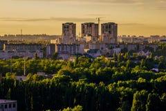 Edificios modernos, zona verde en el fondo de la puesta del sol Fotografía de archivo