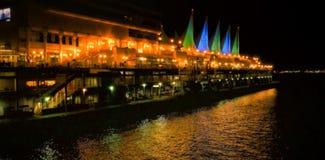 Edificios por el río en ciudad en la noche Imágenes de archivo libres de regalías