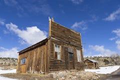 Edificios resistidos viejos del pueblo fantasma en el desierto durante invierno con nieve Foto de archivo libre de regalías