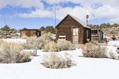 Edificios resistidos viejos del pueblo fantasma en el desierto durante invierno con nieve Fotos de archivo