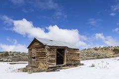 Edificios resistidos viejos del pueblo fantasma en el desierto durante invierno con nieve Imagen de archivo libre de regalías