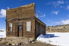 Edificios resistidos viejos del pueblo fantasma en el desierto durante invierno con nieve Foto de archivo