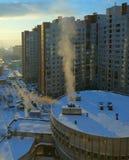 Edificios urbanos nevados del invierno en la puesta del sol Imagenes de archivo